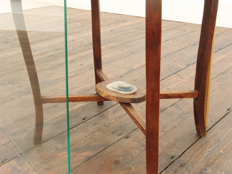 'Further down, leaning against the table, one A1' (detail), wooden table, glass, and shell, 2015